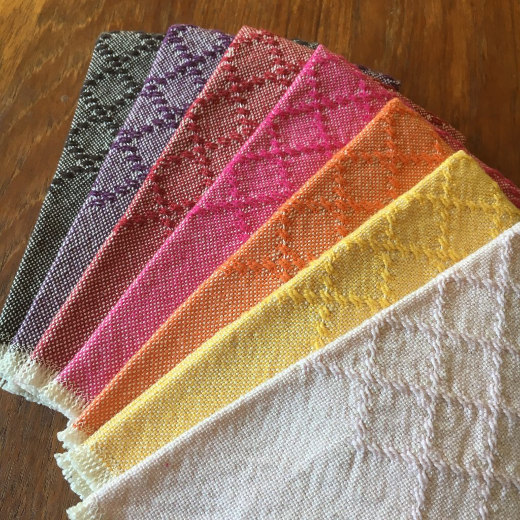 Set of seven colorful huck lace cotton napkins, finished with a simple zigzag stitch and fringe, ready for a picnic