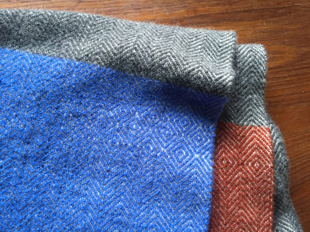 Detail of colorblocked twill poncho with birdseye details